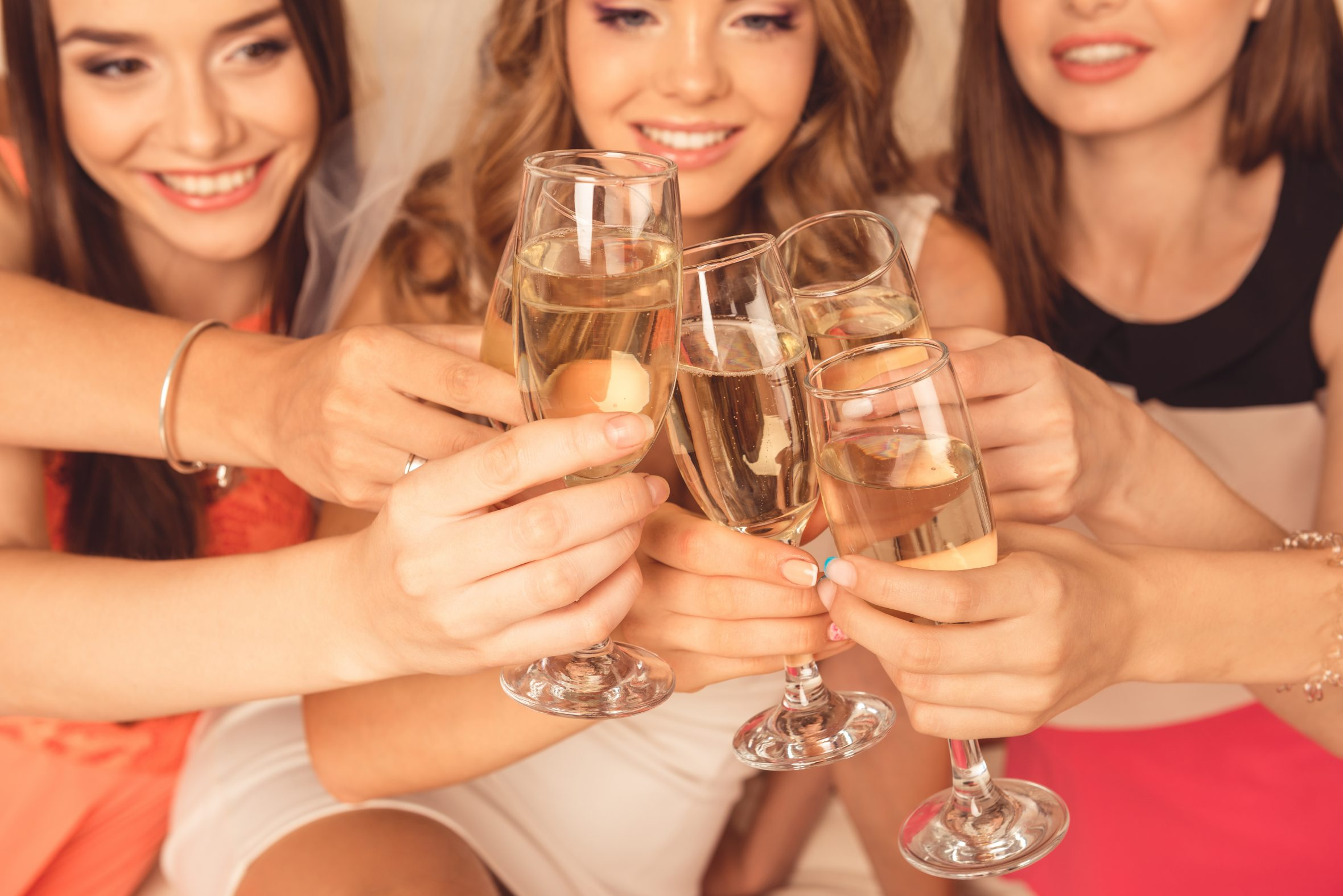 A bridal party clinking wine glasses together